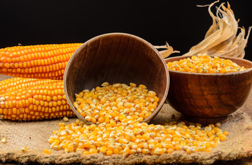Dried corn seed in wooden bowl on wooden table