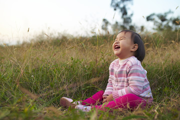 happy little asian girl sitting in the grass