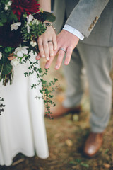 Bride and Grooms Hands with Wedding Rings and Autumn Bouquet
