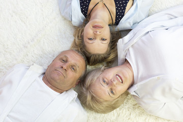 Family lies on the floor head for each other. Top view of happy family of 3 bonding to each other heads and smiling while lying on the h floor