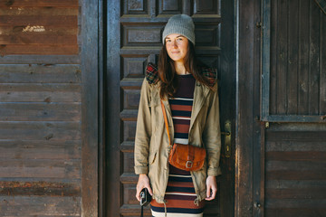 Hipster woman standing in front of a wooden cabin on the mountain.