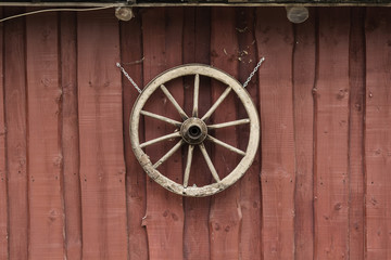 Wooden wheel hanging on a red barn wall