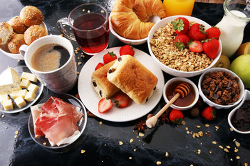 Breakfast served with coffee, orange juice, croissants and strawberry, jam and tea.