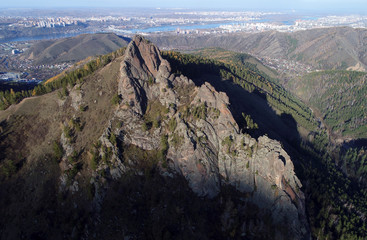 An aerial view shows a rock named the Takmak at the Stolby national nature reserve in the Siberian Taiga area outside Krasnoyarsk seen in the background