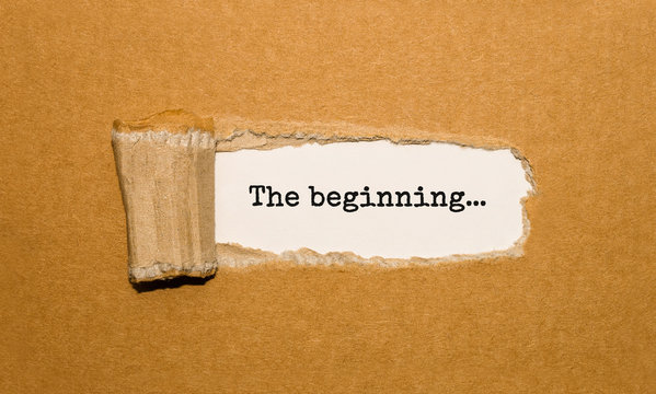 The text The beginning appearing behind torn brown paper