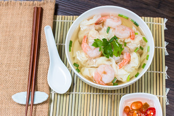 Shrimp wonton noodle soup with braised pork in soup on wooden table - Asian food style.