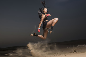 A Beautiful Asian-Black, Mixed Race martial artist female performs kicks, punches and stick fighting with creative leaps in the desert at sunrise or sunset wearing black short tights and black sports  Wall mural