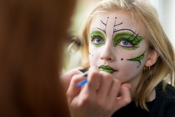 Mother Applying Face Paint Makeup for Little Girl Witch Halloween Costume
