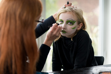 Mother Applying Face Paint Make Up for Girl Witch Halloween Costume