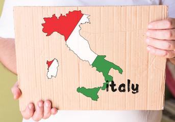 italian map on cardboard in hands man