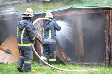 A team of firefighters extinguishes a fire in old wooden buildings
