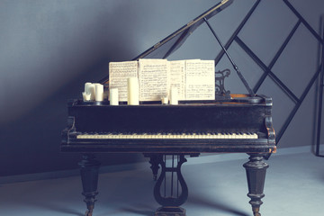 Old piano, rubbed and in scratches. Notes written on paper