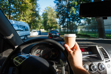 The driver is drinking coffee behind the wheel closeup. Transportation, drinks, people and vehicle concept - close up of man drinking coffee while driving car