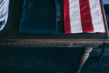 American flag and jeans on a vintage wooden table