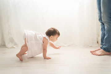 A Little Girl Crawling To Her Mother's Legs
