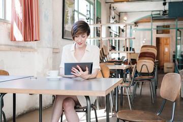 Smiling Woman Using Tablet in Cafe