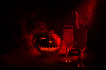 Two glasses of wine and bottle with Halloween - old jack-o-lantern on dark toned foggy background. Scary Halloween pumpkin. Useful as party poster