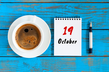 October 19th. Day 19 of october month, calendar on workbook with coffee cup at student workplace background. Autumn time
