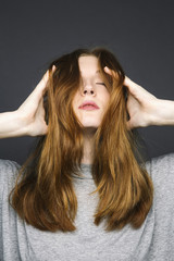 Photo of young redheaded woman with eyes closed