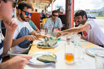 Group of young men having traditional exotic food for lunch in a restaurant outside