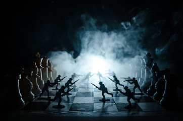 War concept. Silhouettes of soldiers on chessboard. War Concept. Military silhouettes fighting scene on war fog sky background, Chess board game concept of business ideas and competition