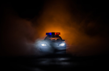 Police car chasing a car at night with fog background. 911 Emergency response police car speeding to scene of crime
