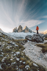 young alpine climber with red jacket looking at the famous three peaks at sunrise
