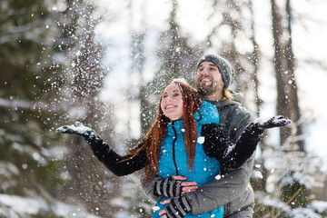 Joyful couple enjoying the snowfall