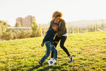 Mother and her son playing football in the park.