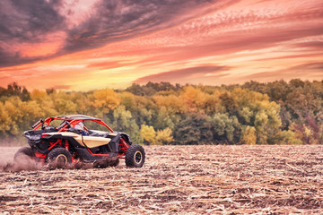Racing quad bike in field under dramatic sunset sky
