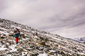 Back view of several hikers climbing snowed and rocky mountain