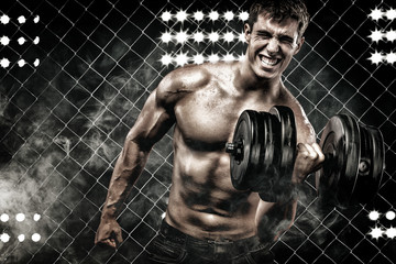 Athletic shirtless young sports man - fitness model holds the dumbbell in gym. Copy space fore your text.