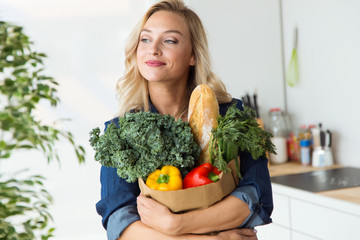 Beautiful young woman grocery shopping bag with vegetables at home.