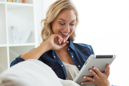 Beautiful young woman using her digital tablet at home.