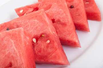 Triangle slices of fresh and juicy watermelon on white plate