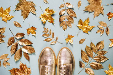 Autumn composition. Pattern made of autumn golden  leaves and stylish shoes on  blue background. Flat lay, top view