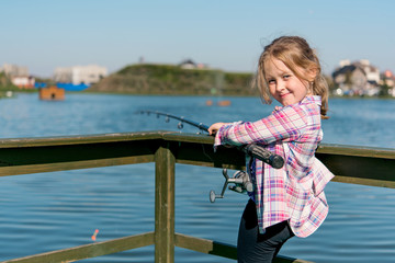 child is fishing on the pier