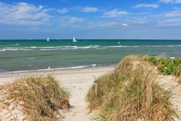 Fototapete - Weg durch Dünen zum Strand an der Ostsee mit blauem Himmel mit Wolken bei Heiligenhafen, Schleswig-Holstein. Mit Segelbooten, Kitesurfern und Möwen.