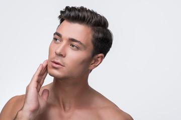 Charming pleasant guy is enjoying his skin