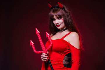 A beautiful, sexy woman in a devil costume, a demon with horns and pitchforks, a trident, in a red dress. American, dress for a costume party Halloween. Choker on the neck. Bright makeup