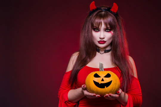 Beautiful, sexy, a woman in a devil costume is holding a pumpkin. American, dress for a costume party Halloween. Your text here