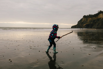 Little girl runs with a stick on a wet wintry beach in the morning.
