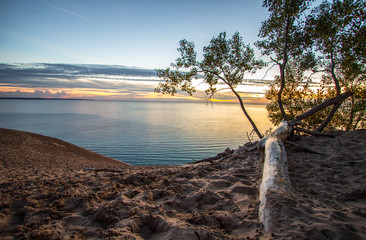 Sand Dune Overlook On Sunset Lake. Massive sand dune in Sleeping Bear Dunes National Lakeshore overlooking a sunset on Lake Michigan.