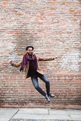 Happy man jumping in front of a brick wall