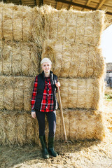 Portrait of a woman farmer with a hoe standing on a haystack.