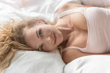Glad smiling lady lying in bed