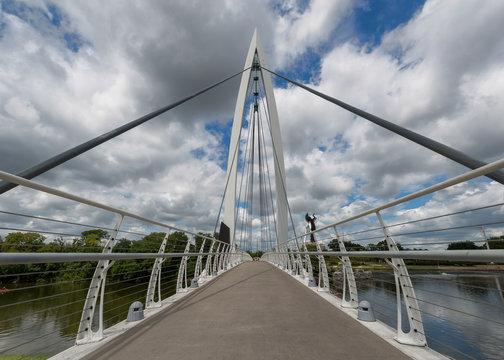 Pedestrian bridge over the Arkansas River by The Keeper of the Plains steel sculpture in Wichita, Kansas