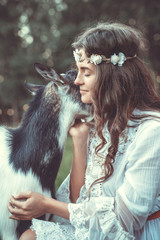Young woman and funny friendly goat