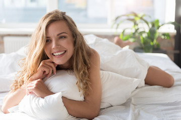 Hilarious smiling young woman in bed