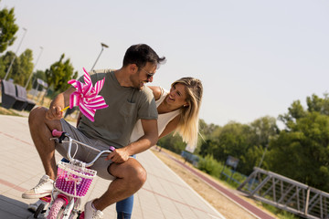 Young couple having fun while riding bike for kids